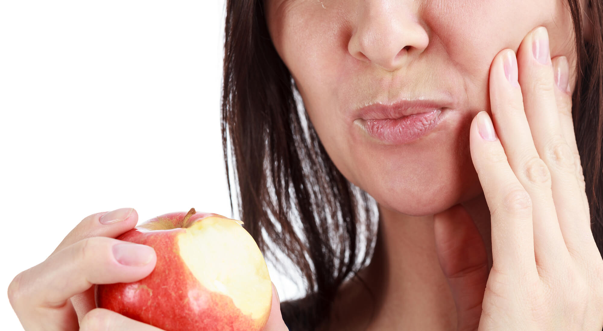 Woman biting on an apple and needing Lake Worth Family Dentistry tooth sensitivity treatment