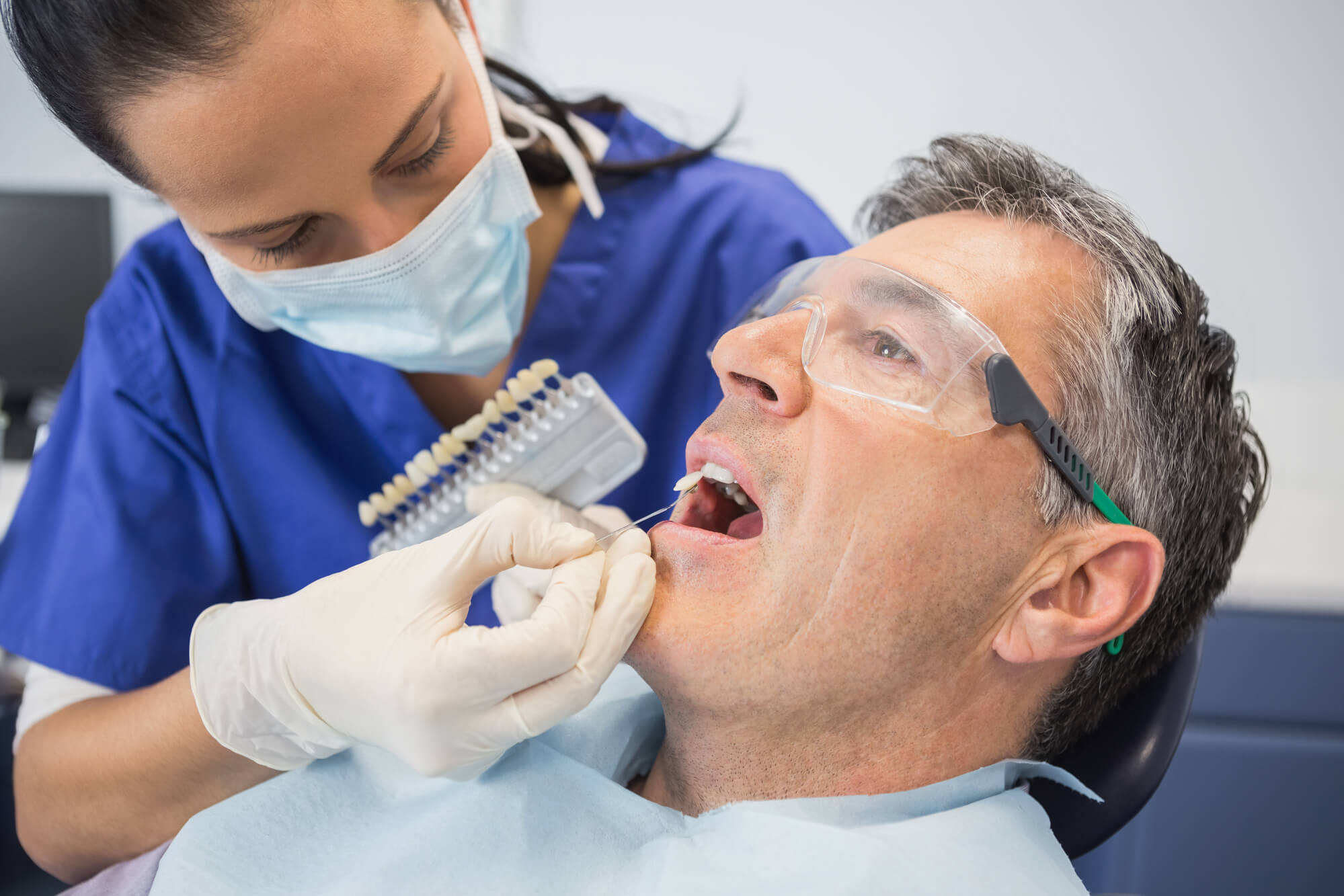 dentist choosing the best shade of whiteness for Greenacres cosmetic dentistry